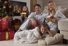 Famiglia felice a casa con i regali di Natale Immagine Stock Libera da Diritti