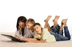Famiglia felice a casa con il computer portatile Fotografia Stock