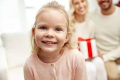 Famiglia felice a casa con il contenitore di regalo di natale Immagini Stock