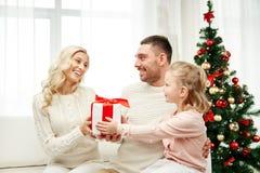 Famiglia felice a casa con il contenitore di regalo di natale Immagine Stock Libera da Diritti