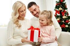 Famiglia felice a casa con il contenitore di regalo di natale Fotografia Stock Libera da Diritti