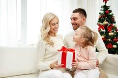 Famiglia felice a casa con il contenitore di regalo di natale Fotografia Stock