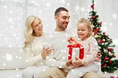 Famiglia felice a casa con il contenitore di regalo di natale Fotografie Stock Libere da Diritti