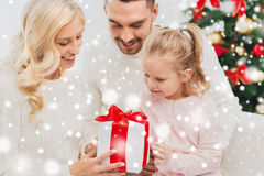 Famiglia felice a casa con il contenitore di regalo di natale Immagine Stock
