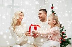 Famiglia felice a casa con il contenitore di regalo di natale Fotografie Stock