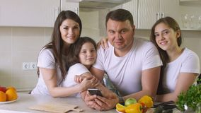 Famiglia felice a casa in cucina, nel sorriso e nell'esame della macchina fotografica immagine stock