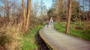 Famiglia felice che cammina insieme tenendosi per mano nel Fotografia Stock Libera da Diritti