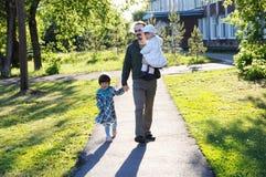 Famiglia felice che cammina nella sosta padre con le figlie al giorno soleggiato papà e ragazze Fotografia Stock