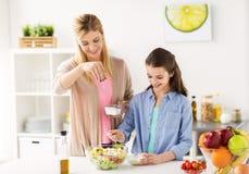 Famiglia felice che cucina la cucina dell'insalata a casa immagine stock libera da diritti