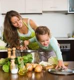 Famiglia felice che cucina minestra Fotografie Stock