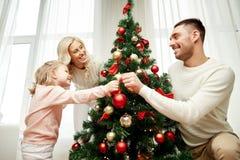 Famiglia felice che decora l'albero di Natale a casa Fotografia Stock