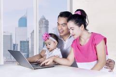 Famiglia felice che esamina computer portatile Fotografia Stock Libera da Diritti
