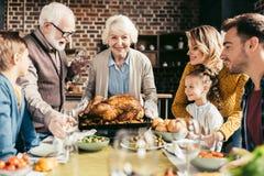 famiglia felice che esamina il tacchino delizioso di ringraziamento in mani fotografia stock