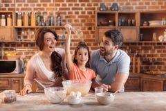 Famiglia felice che fa insieme dolce nella cucina immagine stock