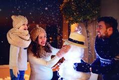 Famiglia felice che fa pupazzo di neve alla luce di sera sotto la neve di inverno fotografia stock libera da diritti