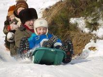 Famiglia felice che fa scorrere giù la collina della neve immagini stock