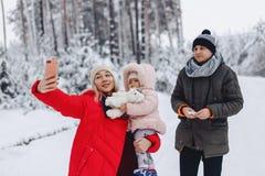 famiglia felice che fa un selfie con la sua piccola figlia fotografia stock libera da diritti
