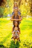 Famiglia felice che gioca come torre nel parco Immagini Stock Libere da Diritti