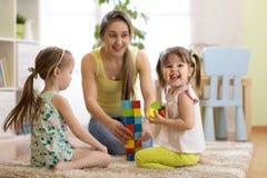 Famiglia felice che gioca con i cubi sul pavimento La madre e le figlie passano insieme il tempo di divertimento Immagini Stock
