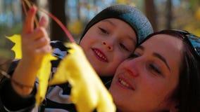 Famiglia felice che gioca con le foglie gialle video d archivio
