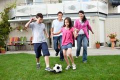 Famiglia felice che gioca gioco del calcio nel loro cortile Fotografia Stock