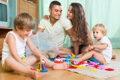Famiglia felice che gioca nell'interno domestico Immagini Stock