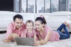 Famiglia felice che gode del tempo libero con un computer portatile fotografia stock