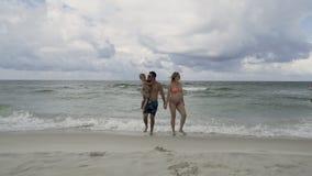 Famiglia felice che gode della passeggiata di mattina sulla spiaggia 4k stock footage