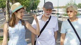 Famiglia felice che gode della vacanza Anziani e la loro figlia che hanno grande tempo che cammina lungo la passeggiata archivi video