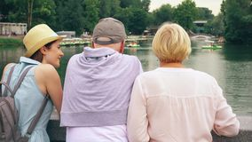 Famiglia felice che gode della vacanza Gli anziani e la loro figlia adolescente fanno una pausa il lago in parco che fanno un gir archivi video