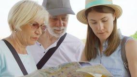 Famiglia felice che gode della vacanza Gli anziani e la loro figlia che studiano la città tracciano il ricerca delle attrazioni stock footage