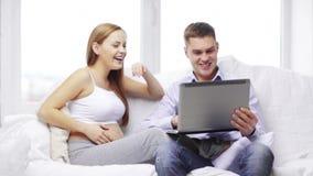 Famiglia felice che guarda con il computer portatile archivi video
