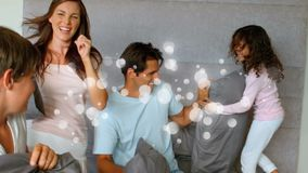 Famiglia felice che ha battaglia del cuscino in camera da letto con effetto della luce archivi video