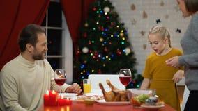 Famiglia felice che ha cena sana di natale, decorazioni che scintillano sull'albero, festa archivi video
