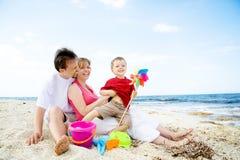 Famiglia felice che ha divertimento sulla spiaggia. Immagine Stock