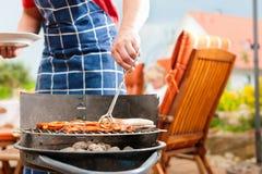 Famiglia felice che ha un barbecue Immagine Stock Libera da Diritti