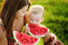 Famiglia felice che ha un picnic nel giardino verde Immagine Stock