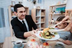 Famiglia felice che mangia insieme i piatti alla tavola Genitori con la loro figlia riunita alla tavola immagine stock libera da diritti