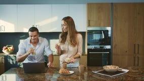 Famiglia felice che mangia prima colazione alla cucina Coppie sorridenti che parlano a casa stock footage