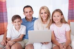 Famiglia felice che per mezzo del computer portatile Fotografie Stock Libere da Diritti