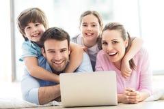 Famiglia felice che per mezzo insieme del computer portatile Fotografia Stock Libera da Diritti