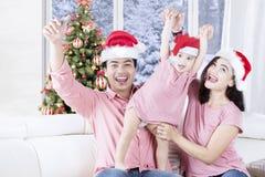 Famiglia felice che porta il cappello di Santa Claus a casa Immagini Stock Libere da Diritti