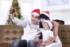 Famiglia felice che prende una foto fotografia stock