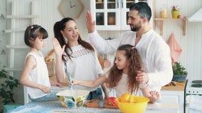 Famiglia felice che prepara alimento sulla cucina, tagliente le verdure, movimento lento video d archivio