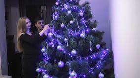 Famiglia felice che prevede il bambino del bambino, decorante l'albero di Natale video d archivio