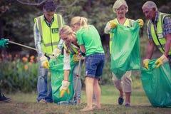 Famiglia felice che raccoglie rifiuti Immagine Stock Libera da Diritti