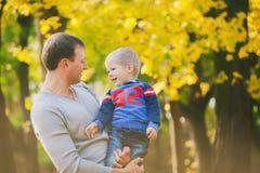 Famiglia felice che ride e che gioca in legno di autunno fotografia stock libera da diritti