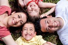 Famiglia felice che risiede nel cerchio sull'erba verde Fotografie Stock