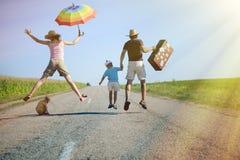 Famiglia felice che salta con la valigia sulla strada campestre Immagini Stock