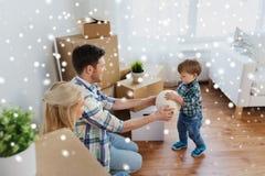 Famiglia felice che si muove verso la nuova casa e che gioca palla immagini stock libere da diritti